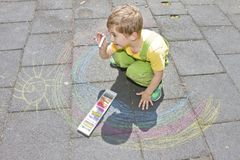 Cute boy draws with colorful chalks on asphalt. Summer activity and creative games for small kids. Child together having fun. Scho stock images
