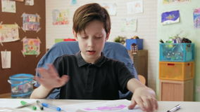 Cute boy draws picture of car and shows it looking at the camera stock video