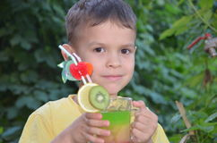 Cute boy drinking healthy cocktail fruits juice smoothie in summer. Happy child enjoying organic drink. stock photos