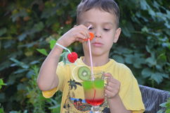Cute boy drinking healthy cocktail fruits juice smoothie in summer. Happy child enjoying organic drink. Stock Photo