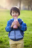 Cute boy, drinking healthy strawberry smoothie in the park. Springtime Royalty Free Stock Photography