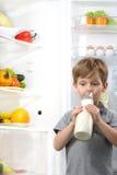 Cute boy drinking milk near open fridge Stock Photos
