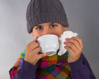 Cute boy drinking tea and wipes a nose with napkin Royalty Free Stock Image