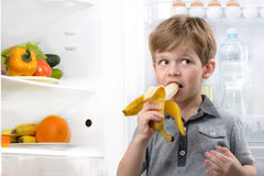 Cute boy eating banana near open fridge Royalty Free Stock Image