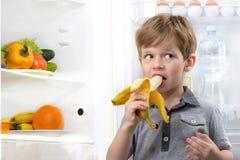 Cute boy eating banana near open fridge Royalty Free Stock Image