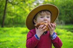 Cute boy eating a croissant. Adorable child biting into a croissant Royalty Free Stock Photos