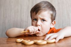Cute boy eating crunchy straw. Small child boy sitting at wooden table stock images