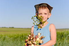 Cute Boy Eating and Holding Green Onions Stock Photography