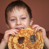 Cute boy is eating pancake Royalty Free Stock Photography
