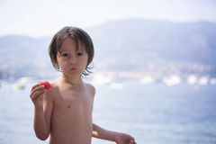 Cute boy, eating piece of watermelon on the beach Stock Photo