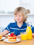 Cute boy eating waffles with strawberries Royalty Free Stock Photos