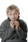 Cute boy eats a chocolate egg Royalty Free Stock Images