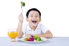 Cute boy eats vegetable salad Stock Photo
