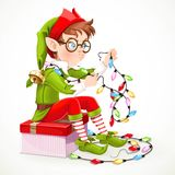 Cute boy elf sitting on box and unravels Christmas garland Stock Photos