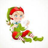 Cute boy elf sitting on the floor and cuts out a snowflake Royalty Free Stock Photography