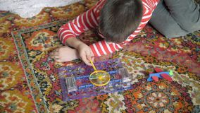 Educational indoor games. Cute boy emotionally engaged in e-project in my room at home on the floor. The kid collects the electric circuit for running the motor stock footage