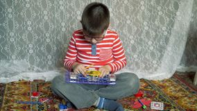 Educational indoor games. Cute boy emotionally engaged in e-project in my room at home on the floor. The kid collects the electric circuit for running the motor stock video