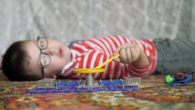 Educational indoor games. Cute boy emotionally engaged in e-project in my room at home on the floor. The kid collects the electric circuit for running the motor stock video footage