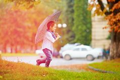 Cute boy enjoying an autumn rain in city park Royalty Free Stock Images