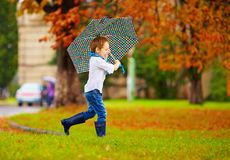 Cute boy enjoying an autumn rain in city park Stock Photos