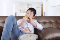 Cute boy enjoying cheeseburger at home Royalty Free Stock Photos