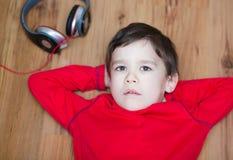 Cute boy enjoying music using headphones Royalty Free Stock Photos