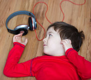 Cute boy enjoying music using headphones Stock Images