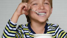 Cute boy European appearance is yogurt. Portrait of a happy child sitting at the table. Ecco, baby food. stock footage