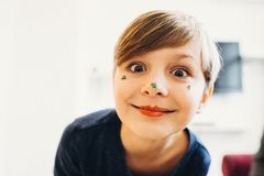 A cute boy with a face painted like a clown. A closeup view of a cute boy with a face painted with eatable bright color cream, smiling with clown lips, blurred royalty free stock images