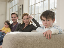 Cute Boy With Family Sitting On Sofa Royalty Free Stock Photos