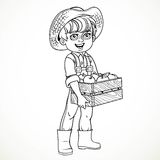 Cute boy farmer in jeans overalls holding a wooen box of apple Stock Photo