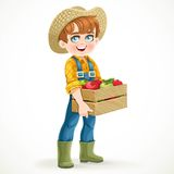 Cute boy farmer in jeans overalls and rubber boots holding a box of apple Stock Photos
