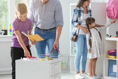Cute boy with father choosing school stationery. In store stock images