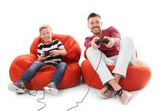 Cute boy with father playing video game. On white background Stock Images