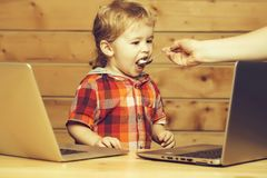 Cute boy fed with spoon. Cute baby boy child with blond curly hair fed with spoon infront of two laptop computers on wooden background royalty free stock photography