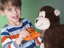 Cute boy feeding his monkey doll with pizza Stock Image