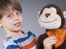 Cute boy feeding his monkey doll with pizza Stock Photos