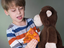Cute boy feeding his monkey doll with pizza Stock Images