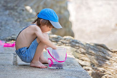 Cute boy with fishing net and bucket, trying to catch some littl. E fishes in the sea on French Riviera royalty free stock images