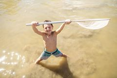 Cute Boy fishing with a net on a lake stock photos
