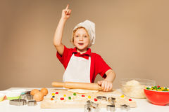 Cute boy flattening dough with rolling pin Royalty Free Stock Images