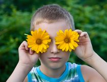 Cute boy with flowers on eyes having fun Stock Photography