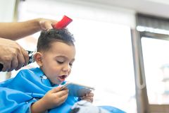 Cute Boy Getting a Hair Cut in a Barber Shop. Beauty Concept royalty free stock image