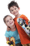 Cute boy and girl are carring skateboards Stock Image