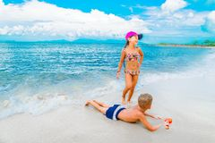 Cute boy and girl  having fun on the sunny tropical beach. Lying on sand, wonderful waves around them. View from above. Stock Photos