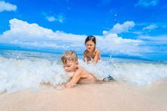 Cute boy and girl  having fun on the sunny tropical beach. Lying on sand, wonderful waves around them. View from above. Royalty Free Stock Image