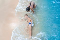 Cute boy and girl  having fun on the sunny tropical beach. Lying on sand, wonderful waves around them. View from above. Stock Photography