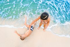 Cute boy and girl  having fun on the sunny tropical beach. Lying on sand, wonderful waves around them. View from above. Royalty Free Stock Photo