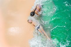Cute boy and girl  having fun on the sunny tropical beach. Lying on sand, wonderful waves around them. View from above. Stock Images