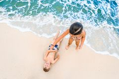 Cute boy and girl  having fun on the sunny tropical beach. Lying on sand, wonderful waves around them. View from above. Stock Image